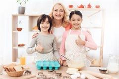 La grand-mère avec ses petits-enfants fait cuire des pâtisseries dans la cuisine Biscuits de cuisson Images libres de droits