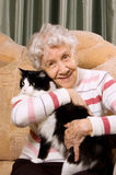 La grand-mère avec un chat sur un sofa Images libres de droits