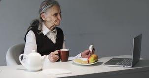 La grand-mère boit du café et mange des biscuits dans le bureau banque de vidéos