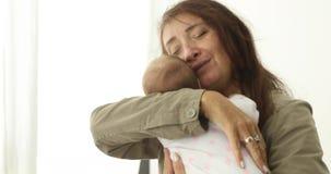 La grand-mère calme le bébé nouveau-né banque de vidéos