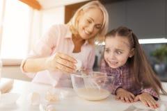 La grand-mère conduit l'oeuf dans la pâte Elle enseigne à sa petite-fille comment faire cuire un gâteau fait maison Photographie stock