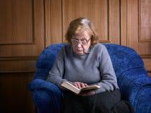 La grand-mère dans un fauteuil avec le livre Images stock