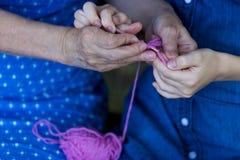 La grand-mère enseigne sa petite-fille à faire du crochet Mains d'aîné Photographie stock libre de droits