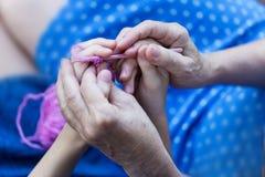 La grand-mère enseigne sa petite-fille à tricoter Mains de vieux woma Photo libre de droits