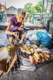 La grand-mère est rôti la banane à vendre Photos stock