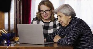 La grand-mère et la dame âgée en verres parlent sur Skype utilisant un ordinateur portable clips vidéos