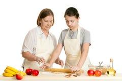 La grand-mère et la pâte de petit pain de petite-fille Photographie stock