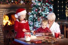 La grand-mère et les enfants font des biscuits cuire au four de Noël Images stock
