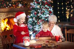 La grand-mère et les enfants font des biscuits cuire au four de Noël Photo stock