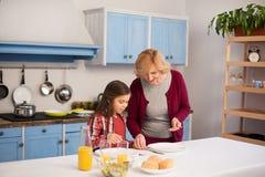 La grand-mère et la petite-fille étendent la table photographie stock