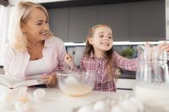 La grand-mère et la petite-fille font cuire un gâteau fait maison Une femme tient un livre des recettes dans des ses mains, regar Images libres de droits