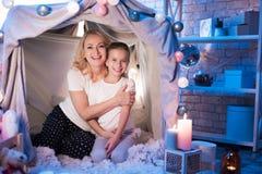 La grand-mère et la petite-fille s'embrassent dans la maison couvrante la nuit à la maison images stock
