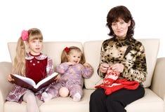 La grand-mère heureuse de famille tricote, livre affiché par enfant. Photographie stock