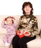La grand-mère heureuse de famille tricote, livre affiché par enfant. Images stock