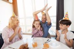 La grand-mère, le grand-père et le frère félicitent la petite fille sur son anniversaire Photographie stock