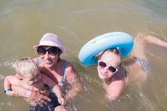 La grand-mère, le petit-fils et la petite-fille nagent dans l'eau dans un swimsuite Photo libre de droits