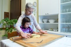 La grand-mère lui enseigne des petits-enfants comment faire des pâtes Images libres de droits