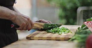 La grand-mère prépare une salade fraîche des légumes dehors banque de vidéos