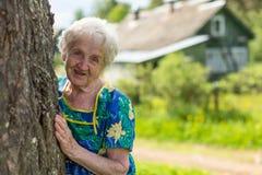 La grand-mère regarde par derrière un arbre Photos stock