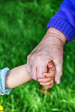 La grand-mère retient la main de childs Photos libres de droits