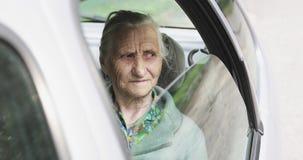 La grand-mère triste monte dans le siège arrière de la voiture banque de vidéos
