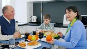 La grand-maman et le grand-père alimentent le petit garçon avec les produits délicieux de boulangerie avec le thé et les fruits banque de vidéos