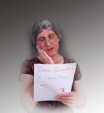 La grand-maman heureuse a affiché la lettre d'amour de crayon de l'enfant Image libre de droits