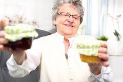 La grand-maman prépare komfitury dans des pots Images stock