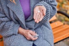 La grand-maman va boire les pilules qui sont dans la main étroite Images libres de droits