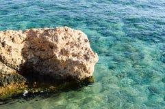 La grande bella pietra marrone, una roccia coperta di fango, alghe nel mare con una scogliera basa contro un fondo dell'acqua blu fotografia stock