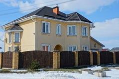 La grande casa marrone dopo un di legno recinta la via nella neve immagine stock libera da diritti