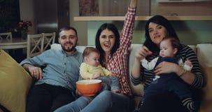 La grande famiglia con il loro bambino che guarda la TV e gode del tempo che mangia insieme il popcorn 4K stock footage