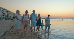 La grande famiglia divertente felice cammina sulla spiaggia sul fondo Pireo, Grecia del tramonto del mare video d archivio