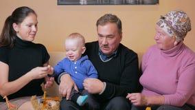 La grande famiglia felice con un bambino la suoi madre e nonni si diverte a casa sullo strato Ridono e parlano fra archivi video