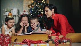 La grande famille gaie de quatre personnes lisent un livre Nuit de nouvelle année au pied de l'arbre de Noël clips vidéos