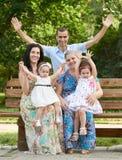 La grande famille s'asseyent sur le banc en bois en parc de ville et l'ondulation, la saison d'été, l'enfant, le parent et la gra Photo libre de droits