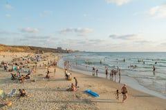La grande folla dei locali ed i turisti sulla spiaggia fronteggiano in Israele Immagine Stock