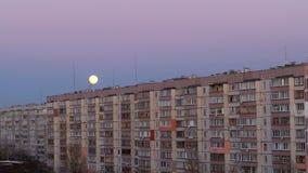 La grande luna piena sopra il tetto di una costruzione a più piani sta alzandosi video d archivio
