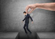 La grande main amène un homme d'affaires au-dessus d'un espace dans le plancher sur le fond gris Photographie stock