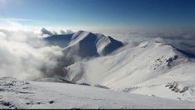La grande montagne au-dessus des nuages forment dans une vallée banque de vidéos