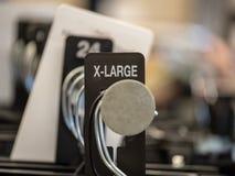la X-grande monture se connectent les vêtements en acier accrochant le support avec des cintres dans le magasin photographie stock libre de droits