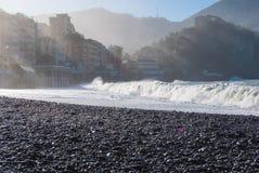 La grande onda sta rompendosi sulla spiaggia delle pietre di Camogli Fotografia Stock