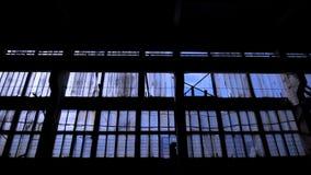 La grande parete di vetro di vecchia costruzione vuota con molte delle finestre, macchina fotografica sta spost indietroare nello stock footage