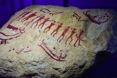 La grande pietra con il disegno basato sull'arte preistorica della roccia Immagine Stock