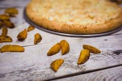 La grande pizza appetitosa incide i pezzi, trovantesi sul bordo con i numeri che indicano il suo diametro 16cm immagini stock