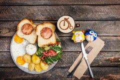La grande prima colazione deliziosa con le uova fritte, le patate fritte, l'insalata fresca, prosciutto del pollo su pane e salsa fotografie stock