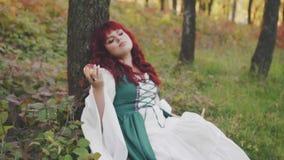 La grande ragazza in un vestito verde lungo è caduto addormentato, pendendo la sua testa su un albero e tenendo una mela meravigl video d archivio