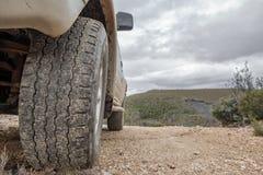 La grande ruota di automobile 4x4 sta sul contesto della montagna Fotografia Stock