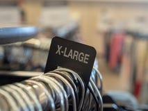 la X-grande section de vêtements d'extra large se connectent le support accrochant en acier avec des cintres dans le magasin image stock