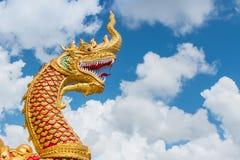 La grande statua dorata del naga con il backg bianco del cielo blu e della nuvola Immagini Stock